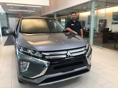 Steve Landers Jr., dealer principal, Steve Landers Cowboy Mitsubishi poses next to a 2020 Mitsubishi Eclipse Cross in his new showroom.