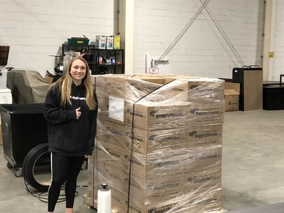 Corinne Cirabisi, HR representative, with packages of non-perishable food items and paper goods to be shipped to each of SupplyHouse.com's distribution centers for their warehouse team.