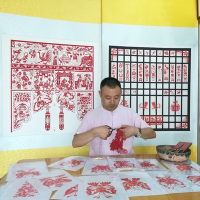 Li Jinbo, a city-level representative inheritor of the national intangible cultural heritage project of Gaomi paper-cutting is creating paper-cutting works featuring a hundred of different dragons.