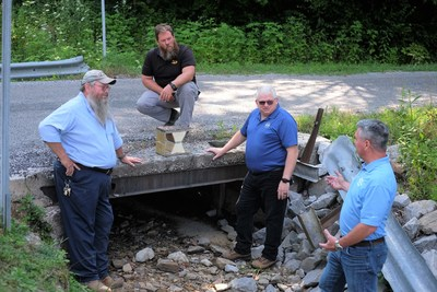IACMI-The Composites Institute Technology Impact Manager John Unser, second from right, is coordinating a public-private collaboration to install a fiber reinforced polymer composite bridge deck in a rural Tennessee community. From left, are Morgan County (TN) Highway Superintendent Joe Henry Miller, McKinney Excavating (TN) Owner Brian McKinney, and Composite Applications Group CEO Jeff McCay.