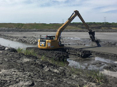 A M.J. Van Damme Inc. excavator digging an Ohio drainage ditch during a springtime restoration project.