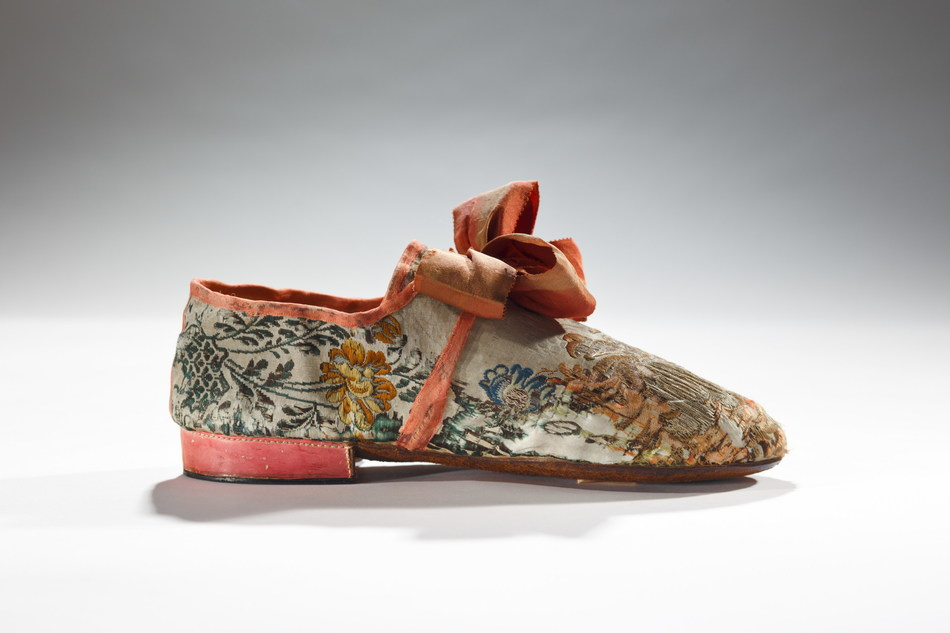 This man's shoe would have been used to express both gender and class. Its low heel conveyed that it was masculine and the expensive fabric and ostentatious bow conveyed that it was upper class.  Its use of pink might confuse us today, but in the 18th century pink was not gendered. 1760-80, English (CNW Group/Bata Shoe Museum)