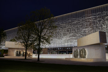 Framing the new Dwight D. Eisenhower Memorial, lit at night, is a stainless steel woven tapestry depicting the Normandy coastline in peacetime.