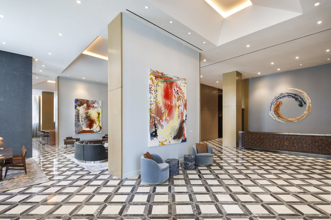The lobby at The Joseph, a Luxury Collection Hotel, Nashville, features a custom-designed reception desk with leather paneling by Lucchese, and ceramic art by artist Brie Ruais (behind desk) and paintings by artist Jackie Saccoccio.