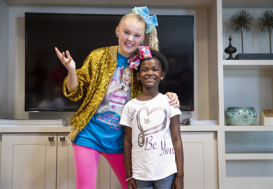 YouTube star and St. Jude Celebrity Ambassador JoJo Siwa (left) shares a moment with St. Jude patient Alana (right), a fellow bow enthusiast, during a tour of St. Jude Children's Research Hospital in September 2019. Siwa is joining dozens of other celebrities for the 30 Days #forStJude campaign.