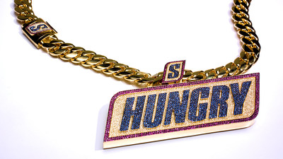 """The second installment of the SNICKERS chain is once again hand-crafted by renowned jeweler, Ben Baller, featuring more than 31 carats of 2,374 brilliant-cut diamonds, blue sapphires and red rubies highlighting the word """"HUNGRY"""" and the iconic """"S"""" from the SNICKERS brand logo. Every week, SNICKERS will award the SNICKERS chain to the NFL player who demonstrated a momentous hunger for the game."""