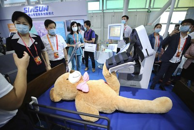 Visitors watch how a robot helps patients recover at the 2020 China International Fair for Trade in Services in Beijing on Saturday, Sept 5, 2020. [Photo by Zhang Wei/China Daily]