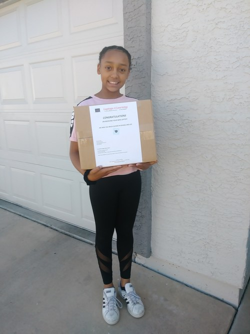 Mariyah Redden, a student at Desert Palms Elementary School shows off the laptop she received from Laptops 4 Learning,