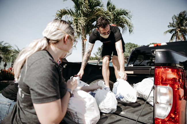 """Convoy of Hope volunteers in Florida pack bags of groceries for distribution as part of their """"100 Million Meals and Counting"""" initiative."""