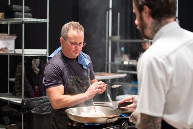 Chef Paul Kahan preparing a meal for guest at the Pilot Light Feed Your Mind Gala