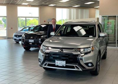 Sean Grant, Dealer Principal, Landmark Mitsubishi poses with a lineup of Mitsubishi vehicles in his new showroom.