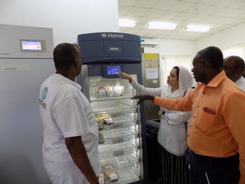 Helping Hand for Relief and Development staff examining new blood storage refrigerator in Zanzibar.