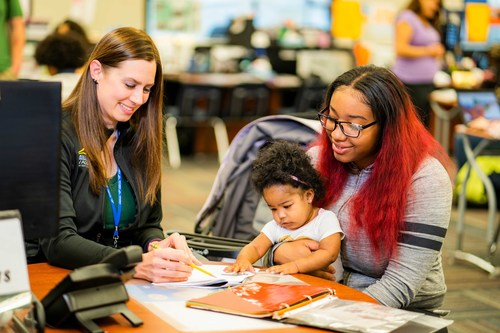 A Learn4Life student learns in a one-on-one interaction with her supervising teacher while holding her baby