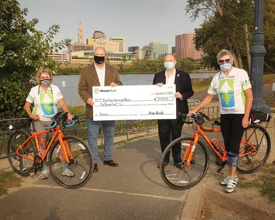 Brian Runkle, Head of Bank Operations for Webster Bank, left, presents a check for $5,000 to Bruce Donald, Tri-State coordinator for the East Coast Greenway Alliance on the Greenway at Great River Park in East Hartford. Joining them were East Coast Greenway Alliance Ambassadors Barbara Amodio, left and Beverly Duncan, right.