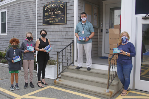 Dr. Thomas Kenworthy, superintendent of Portsmouth, RI schools, (center) accepts mask donations from Embrace Home Loans Director of Communications Jennifer O'Neill (left) and Loan Officer Dawn Ryan (right). Also pictured are students Eoin Soler and Norah Mateos.
