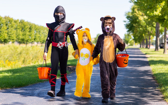 Three children dressed up in costumes with matching masks
