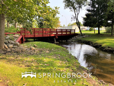 Residents at the Springbrook Estates community enjoy beautiful natural amenities including lush greenery and a creek.