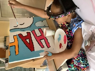 """Flying High with Woodstock: Young patient Za'Naii Roundtree shows off her awesome painting skills as she contributes to a new Snoopy and Woodstock mural at Gillette Children's in St. Paul, Minnesota—hometown of Peanuts creator Charles Schulz. The mural is one of 70 being donated to hospitals worldwide by Peanuts Worldwide and the nonprofit Foundation for Hospital Art as part of the global """"Take Care With Peanuts"""" initiative, launched October 2in conjunction with the 70th Anniversary of Peanuts (CNW Group/Peanuts Worldwide)"""
