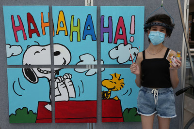 """Tools of the Happiness Trade, Peanuts-Style: At The Children's Hospital at Westmead in Sydney, Australia, patient Bella Conciatore celebrates the new Snoopy and Woodstock mural she helped paint, which will hang in the hospital as a gift from Peanuts Worldwide and the nonprofit Foundation for Hospital Art. The mural is one of 70 being donated to hospitals worldwide as part of the global """"Take Care With Peanuts"""" initiative, launched October 2 in conjunction with the 70th Anniversary of Peanuts. (CNW Group/Peanuts Worldwide)"""