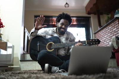 Enseñanza de guitarra acústica a través de una videollamada, haciendo gestos al laptop