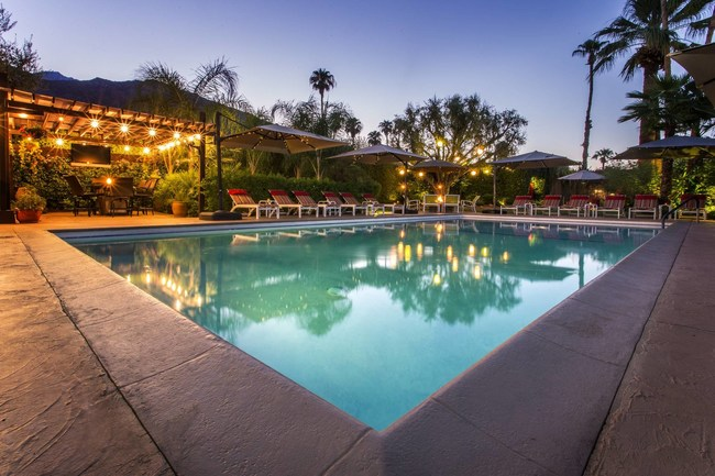 Evening photo of Desert Riviera Hotel's heated pool and guest barbecue area on the left.