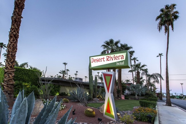 The Desert Riviera sign, surrounded by desert landscaping and palm trees, welcomes guests.