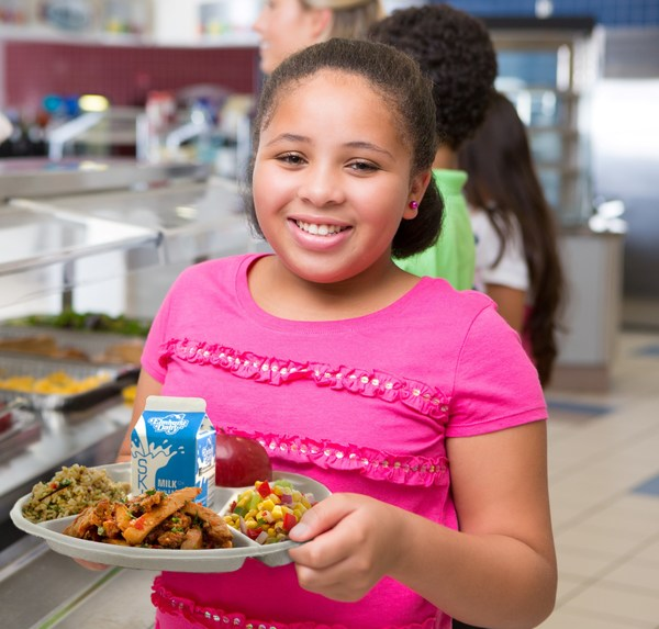 Picture of a student holding up a lunch tray with healthy food