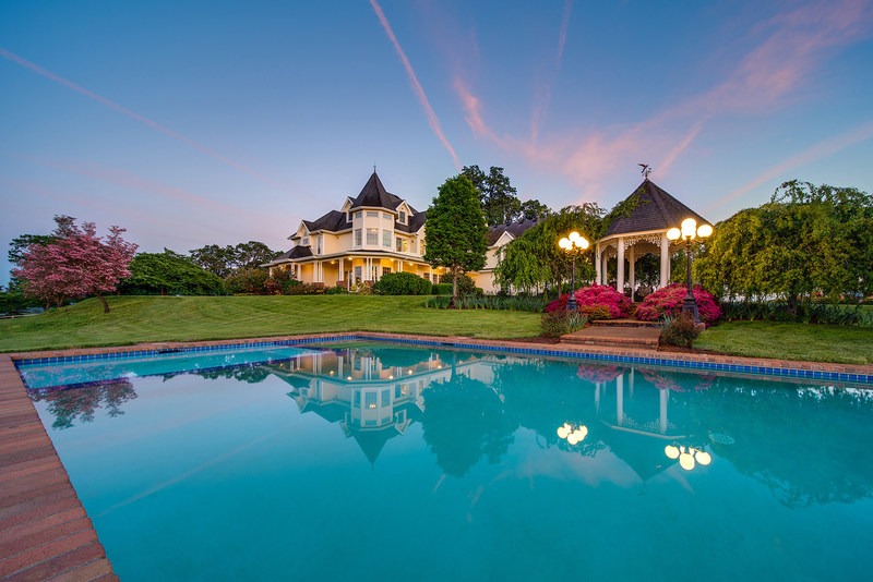 The residence and pool in the evening glow. Also pictured is a lovely, poolside gazebo surrounded by fresh flowers and plantings. The property also boasts a large, outdoor living area that includes a custom-built summer kitchen with fire pit, pizza oven and bar with seating for 12 guests. Learn more at OregonLuxuryAuction.com.