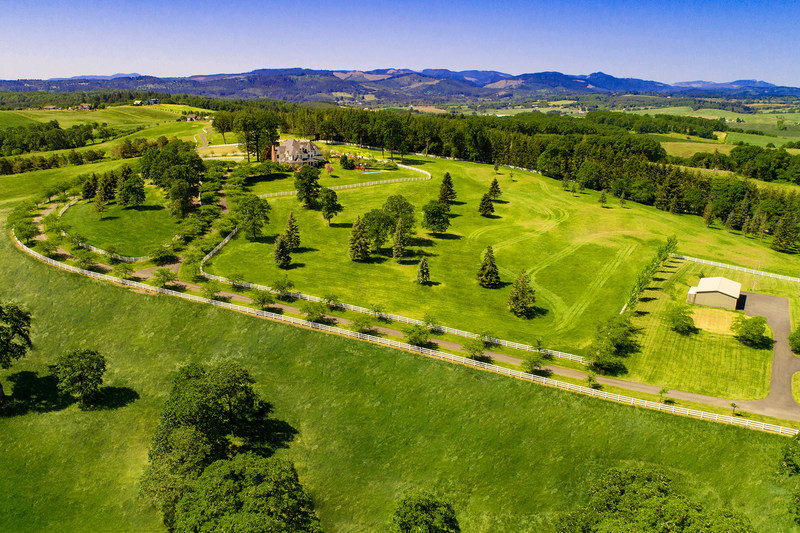 The 7,500-sf residence is perched atop a gently rolling hill, affording beautiful views of the surrounding hills and valleys. There are ample pastures for horse grazing, and a large barn on the property constructed in blue pine. Approx. 128 of the property's 180 acres are suitable for vineyards. Learn more at OregonLuxuryAuction.com.