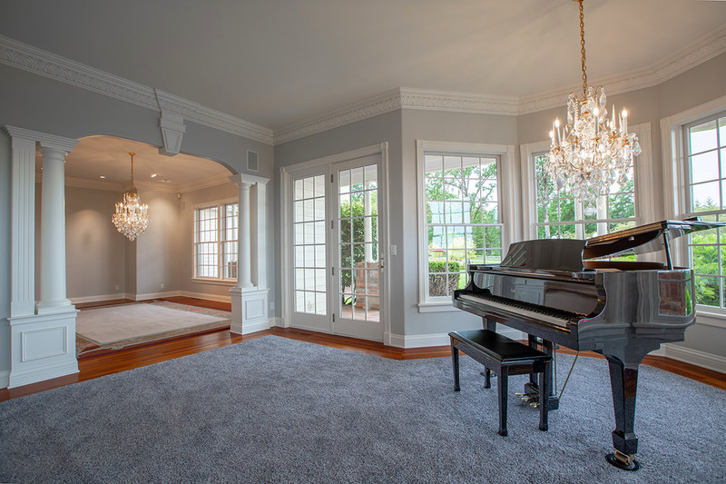 "Interiors are done in a ""relaxed luxury"" style, as shown here in the entry level's music room. The main residence offers approx. 7,500 square feet, with 5 beds and 6.5 baths. Learn more at OregonLuxuryAuction.com."