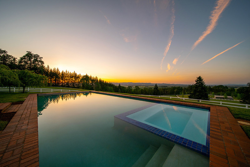 Relaxing and seductive sunset views – as the sun sinks behind the surrounding hills and valleys – can be enjoyed from the estate's custom pool and spa. Learn more at OregonLuxuryAuction.com.
