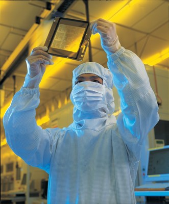 TSMC fabrication operator examining a mask reticle for 12-inch wafers.