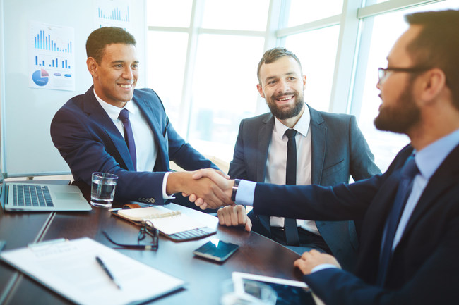 Happy businessmen handshaking after negotiation in office.
