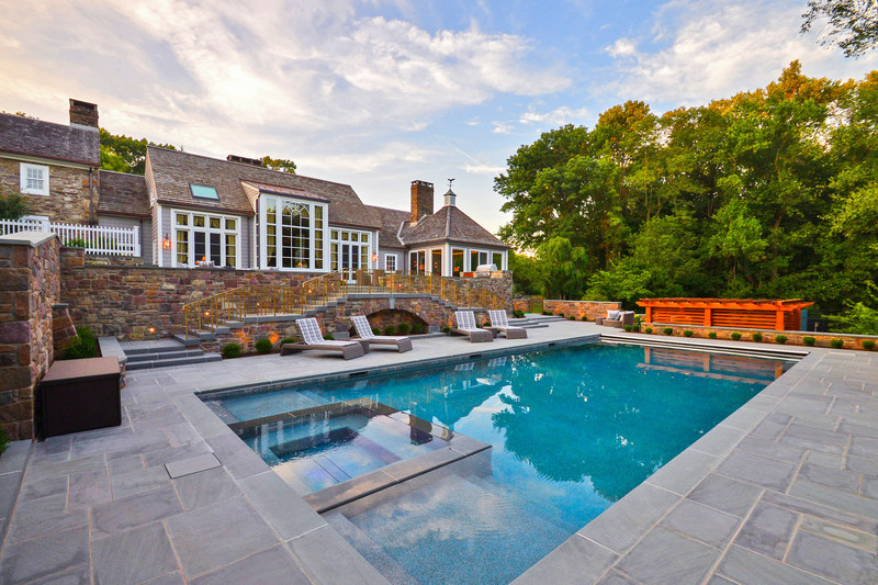Hand-laid bluestone was used extensively in the outdoor living areas, which include a summer kitchen, lounge area with firepit, a heated, 34,000-gallon saltwater pool with infinity-edge spa and electronic solar cover, and lighted walkways and landscaping. NewJerseyLuxuryAuction.com.