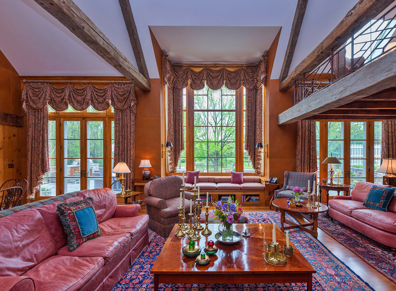 """The residence's grand salon features a soaring cathedral ceiling, with hand-hewn beams reclaimed from NYC's famed Fraunces Tavern and one of the Adirondack """"great camps"""" of upstate New York. The salon includes a wood-burning fireplace, wet bar, and a decorative wall covered in American Bison leather (not pictured). Large windows allow for ample, natural light. NewJerseyLuxuryAuction.com."""