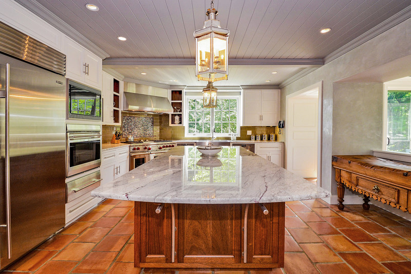 Seen here, the residence's kitchen. The large, center island is mahogany with a marble top. Overhead lanterns were hand crafted in London in sterling silver. A lovely sunroom (not shown) is adjacent to the kitchen. NewJerseyLuxuryAuction.com.