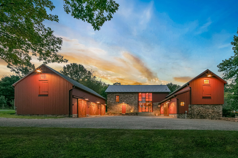 """Stone Creek Farm's unique, 3-part barn complex offers a central structure with beautiful wood and stone interiors – an ideal venue for parties, a fitness center or """"modern man cave"""" – and a lower-level garage. Two utility barns flank the central building, both with upper-level storage lofts. All barns are heated, and are built upon portions of the historic farmhouse's stone walls. NewJerseyLuxuryAuction.com."""