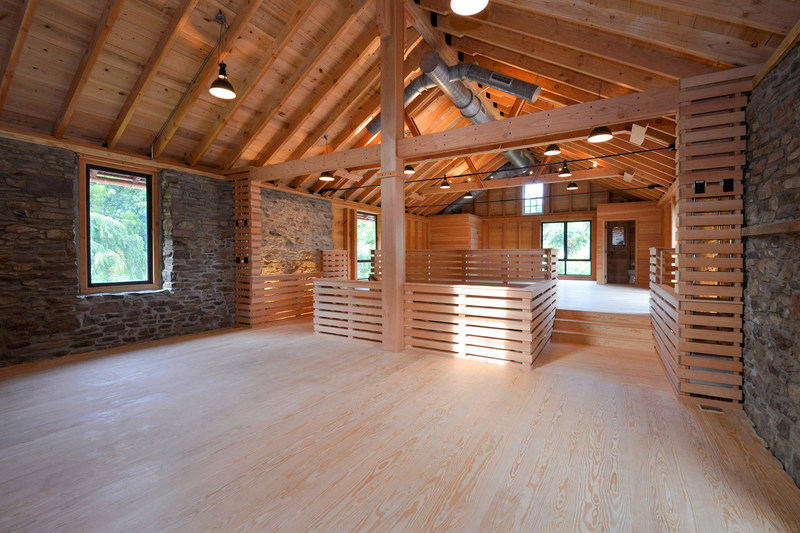 """Inside the central barn's upper level. Post-and-beam construction includes the use of fir, cedar, cypress and yellow pine woods. Black steel rods and ties, slatted walls and wrought iron railings create a modern, """"polished industrial"""" feel. The building has been used by the owners for hosting events at the property, including a few private weddings for friends. NewJerseyLuxuryAuction.com."""