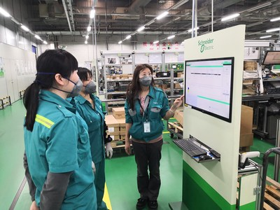 Staff members discuss work plans at French industrial group Schneider Electric's plant in Putuo district