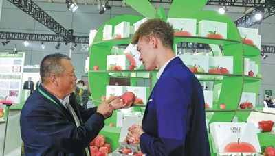 An exhibitor at the first China Shandong International Apple Festival shows his fruit to a foreign visitor. ZHANG DANDAN/CHINA DAILY
