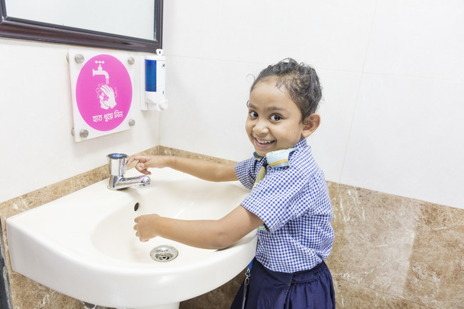 A girl washes her hands at a public toilet in Bangladesh. Kimberly-Clark and its Andrex brand have partnered since 2017 with WaterAid to transform public sanitation services in Bangladesh through the construction and management of inclusive public toilets. Credit: WaterAid/Jannatul Mawa, November 2019