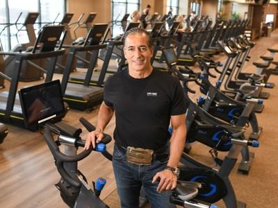 Bahram Akradi leans on a stationary bike at Life Time.