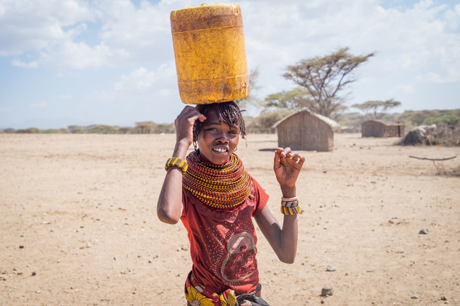 Young woman carrying water from a Well Aware water source in Kenya. Photo Credit: Lindsey Reed