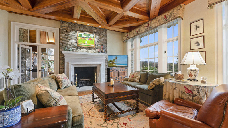 Those who always gravitate towards the coziest areas of the house will love the family room, which features beautiful, wood-beam ceilings and a handsome fireplace with stone surround. A fully-enclosed sunroom with a barbecue grill and walls of windows is situated just off the family room (entry shown above, left of fireplace). Details at LigonierLuxuryAuction.com.