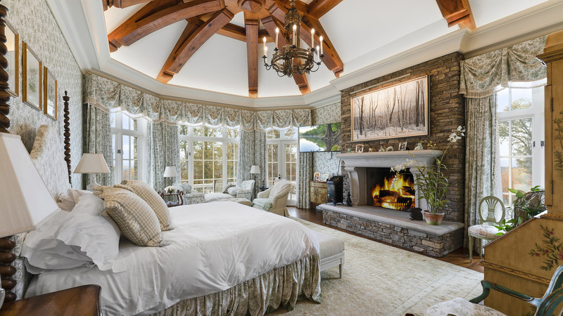 The sprawling master suite echoes the core design elements present throughout many of the main living areas, with exposed beam-work and a handsome fireplace providing the classic ambiance of a posh, countryside home. The lofted, domed ceiling and walls of windows add warmth and natural light. Discover more at LigonierLuxuryAuction.com.
