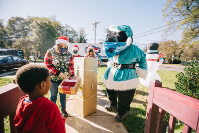 Lowe's associates and Carolina Panthers mascot Sir Purr deliver a Christmas tree to a family in Charlotte, N.C. Lowe's announced it will partner with the NFL and nonprofit organizations to donate $1 million in Christmas trees to families hit hardest by the pandemic.