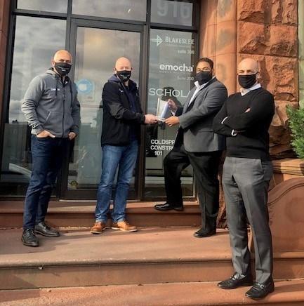 L-R Marc Bandini, Ostendio President and COO and Grant Elliott, Ostendio CEO and chairman present award to Ramon Castro, emocha CTO and Sebastian Seigeur, emocha CEO outside the emocha offices in Baltimore, MD.