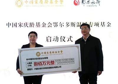 Zhao Kui (right), vice chairman with Erdos Resources Co., Ltd. donates a check to the China Soong Ching Ling Foundation.