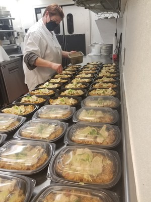 Jackie Bruce prepares hundreds of individually packaged stir fry dishes at Timothy's Restaurant for Meijer team members in Lincoln Township, Mich.