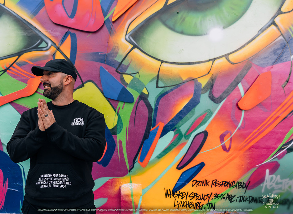 ABSTRK in front of his mural made in collaboration with Jack Daniel's® Tennessee Apple in Miami, FL.
